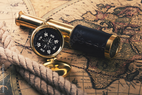 Fotobehang Schip adventures concept - vintage compass and spyglass on old world map