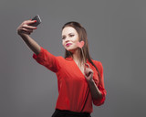 Girl in red shirt, gray background. Joyful young fashion brunette woman doing selfie with smartphone, holds paper heart. Positive emotion feeling, smiling.
