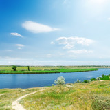 river and green landscape, blue sky with sun and clouds