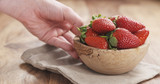 young female hand puts bowl of strawberries on table, 4k photo