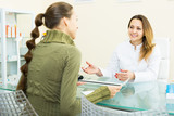 Visitor consulting woman beautician in aesthetic center