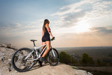 Pretty young fit woman riding on the sports bicycle on the mountain hill with beautiful landscape at the sunset. Pink Kinesio tape glued on the girls hand. Adventure travel in mountains on bike.