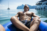 Rear view of a man on a raft relaxing drifting along the river in Phuket, Thailand