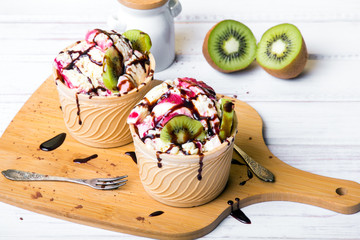 Delicious ice cream in a cup with chocolate sauce and tasty fruits