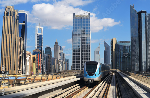 Metro train moving through the skyscrapers Poster