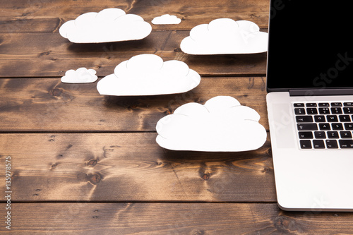 Foto Murales Cloud computing concept laptop close up with white clouds coming out of the computer indicating online storage and internet connection.