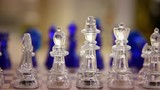 Slow Panning Shot of Glass Chess Pieces on Chess Board