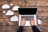 Cloud computing technology concept with white fluffy clouds next to the laptop. Mans hands typing the the keyboard uploading data, on a wooden table. - 136013319