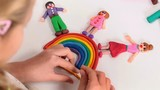 Happy people over the rainbow made from modeling clay - little girl completing an art project