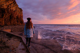 young woman hiker standing on seashore near cliff during sunrise