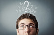 thinking teen with many question marks above his head