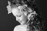 Monochrome photography of a beautiful little girl with orchid flowers