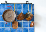 Kitchen interior with vintage copper utensils. old style cookware set. Pan pots, spoon, skimmer hanging on blue tile wall. Copy space, white background photo