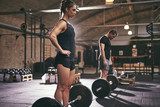 Fit people standing near barbells in gym