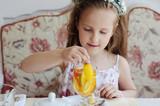 маленькая девочка пьет чай  в ресторане