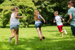 group of happy kids or friends playing outdoors