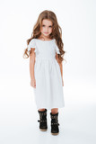 Full length of charming little girl in white dress walking