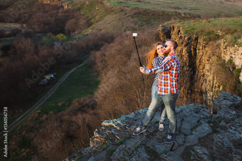 Poster Man and woman make selfie at the top of the mountain.