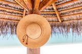 Sun hat hanging on sunshade umbrella on tropical beach. Maldives.