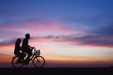 Silhouette of couple on bike.