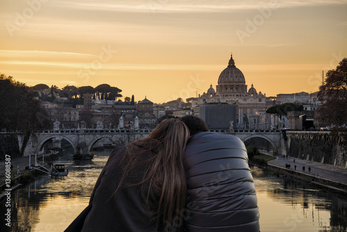 Poster girl and boy hugging each other in front of the city of Rome