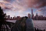 girl and boy hugging each other in front of the new york city at night