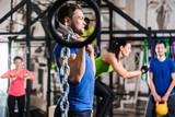 Fototapety Man lifting dumbbell in functional training gym session