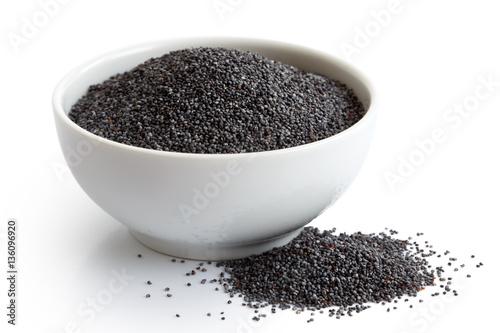Dry poppy seeds in white ceramic bowl isolated on white.