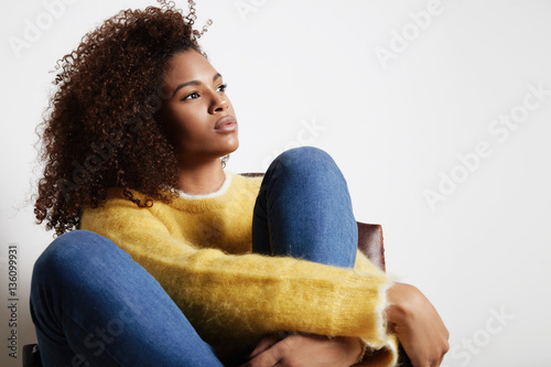black woman hugs her legs and watching aside Poster