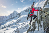 Mountaineer with skiers climbing up a rock in the mountains in winter