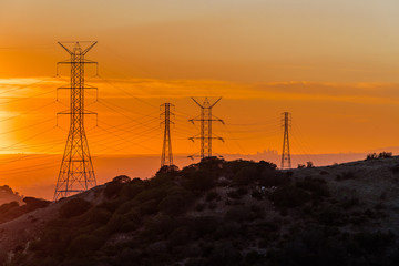 Los Angeles skyline at sunset viewed from afar through power lines.