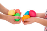 pile of colorful easter eggs in two child hands