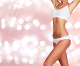 Slim woman body on an abstract background with blurred lights