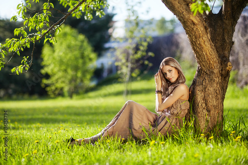 Poster Beautiful young woman dressed in boho style sitting on green gra