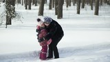 Little girl and her grandmother are running towards each other and joyfully hugging in winter snowy forest. Slow motion.