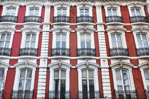 red painted brick facade with white decorations around arched