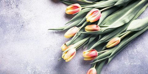 Beautiful yellow orange tulips on light stone background. Mother day, wedding greeting card. Copy space. Retro style toned.