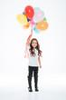 Full length of smiling little girl holding colorful balloons