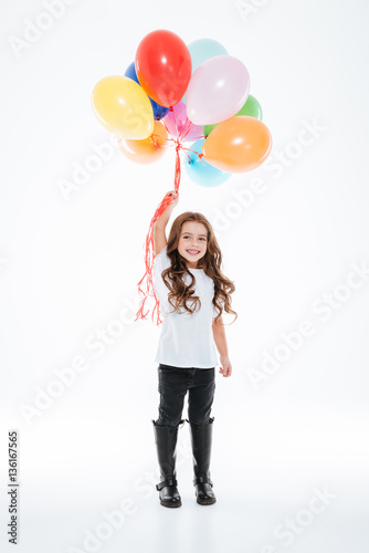 Full length of smiling little girl holding colorful balloons Poster