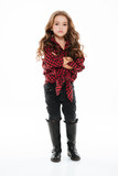 Pretty little girl in plaid shirt standing with arms crossed