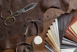 Fototapety Crafting tools on natural cow leather in the tailoring workshop. Top view.