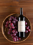bottle of red wine with grape