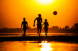 silhouette of kids playing football on the beach.