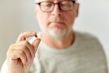close up of senior man with medicine pill