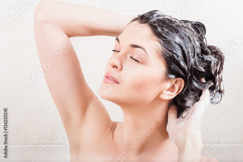 Young woman washing hair with shampoo in the shower