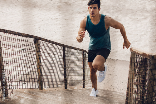 Fitness man running up the steps on beach