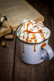 Concept of home relaxation: aromatic coffee or hot chocolate with whipped cream and caramel and old vintage book, copy space