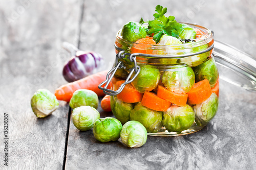 Pickled Brussels sprouts with carrots in glass jar