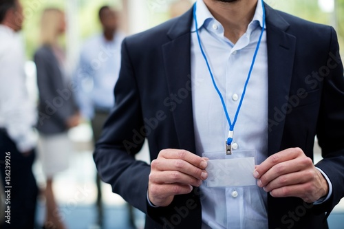 Mid section of employee showing Id card