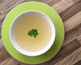Chicken broth with green parsley on top. White bowl of chicken bouillon on wooden background. Top view.